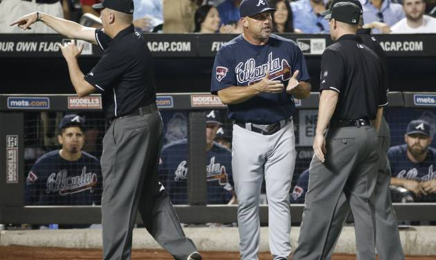 Third base umpire Mike Everitt (57), the crew chief, tosses Atlanta Braves manager Fredi Gonzalez from the game as Gonzalez  argues the call on a second base play in a tie-game in the ninth inning of a baseball game against the New York Mets in New York, Monday, July 7, 2014. (AP Photo/Kathy Willens)