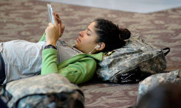 National Guard member Alex Liriano checks messages on her tablet as she waits out flight delays at Hartsfield-Jackson International Airport two days after a winter snow storm, Thursday, Jan. 30, 2014, in Atlanta. More than 400 flights in and out were canceled by 6 a.m. Thursday, according to data from the flight tracking service FlightAware. Many of those flights were canceled before the day began.  (AP Photo/David Tulis)