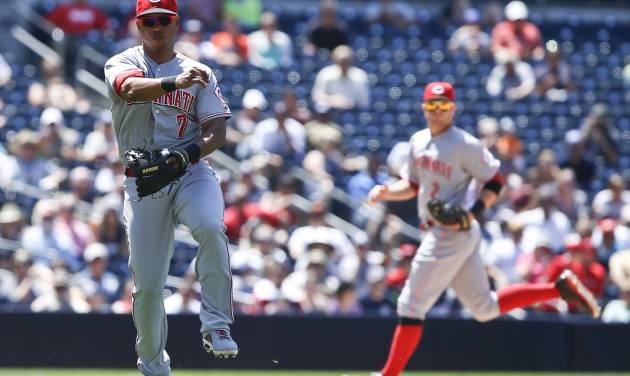 Cincinnati Reds third baseman Ramon Santiago, left, makes the running  throw to first to get the out on San Diego Padres' Chris Denorfia in the seventh inning of a baseball game on Wednesday, July 2, 2014, in San Diego.  The Padres won 3-0. (AP Photo/Lenny Ignelzi)