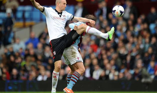 Aston Villa's Grant Holt, rear, and Fulham's Brede Hangeland battle for the ball during the English Premier League soccer match at Villa Park, Birmingham, England, Saturday April 5, 2014. (AP Photo/PA, Joe Giddens) UNITED KINGDOM OUT  NO SALES  NO ARCHIVE