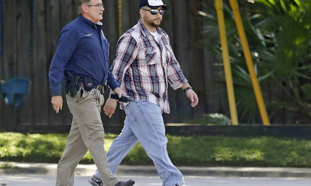 George Zimmerman, right, is escorted to a home by a Lake Mary police officer, Monday, Sept. 9, 2013, in Lake Mary, Fla., after a domestic incident in the neighborhood where Zimmerman and his wife Shellie had lived during his murder trial. Zimmerman's wife says on a 911 call that her estranged husband punched her father in the nose, grabbed an iPad out of her hand and smashed it and threatened them both with a gun. Zimmerman was recently found not guilty for the 2012 shooting death of Trayvon Martin. (AP Photo/John Raoux)