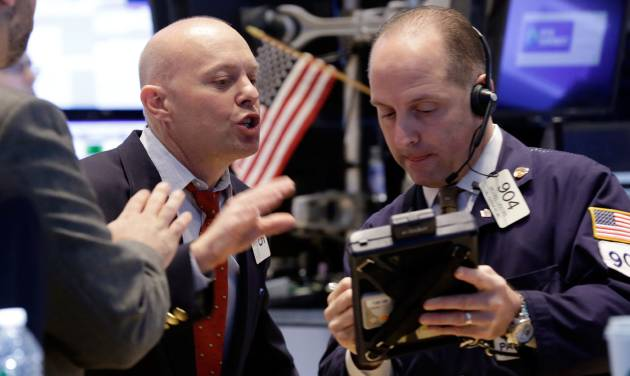 FILE - Traders Daniel Leporin, left, and Michael Urkonis work on the floor of the New York Stock Exchange in this April 23, 2014 file photo. Global stocks tumbled Friday April 25, 2014 after tensions over Ukraine mounted and Standard & Poor's cut Russia's credit rating, warning of capital flight and risks to investment due to the crisis. (AP Photo/Richard Drew, File)