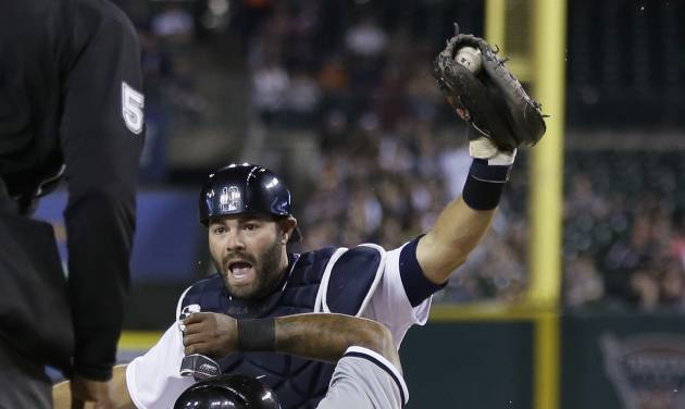 Detroit Tigers catcher Alex Avila holds up the ball to umpire CB Bucknor after tagging Chicago White Sox runner Dayan Viciedo during the seventh inning of a baseball game in Detroit, Monday, April 21, 2014. Viciedo was called safe after the umpire review. (AP Photo/Carlos Osorio)