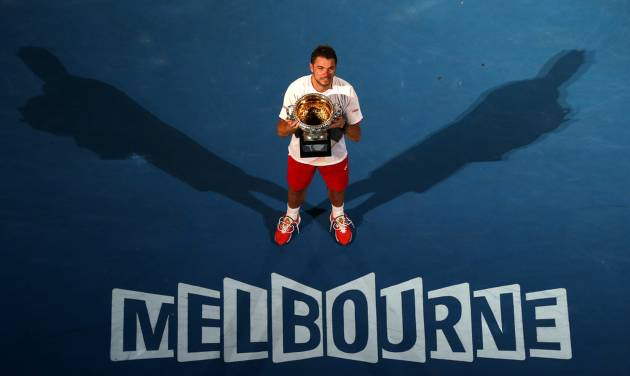 Stanislas Wawrinka of Switzerland holds the trophy after defeating Rafael Nadal of Spain in the men's singles final at the Australian Open tennis championship in Melbourne, Australia, Sunday, Jan. 26, 2014.(AP Photo/Eugene Hoshiko)