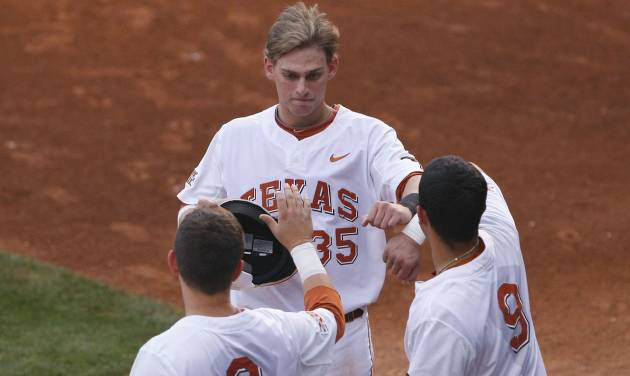 Texas' Madison Carter (35) celebrates with teammates after scoring a run  in the first inning of a second-round game against Oklahoma State in the Big 12 conference NCAA college baseball tournament in Oklahoma City, Thursday, May 22, 2014. (AP Photo/Alonzo Adams)
