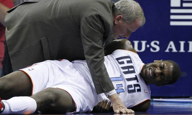 A trainer checks on injured Charlotte Bobcats' Michael Kidd-Gilchrist (14) during the first half of an NBA basketball game against the San Antonio Spurs in Charlotte, N.C., Saturday, Dec. 8, 2012. (AP Photo/Chuck Burton)