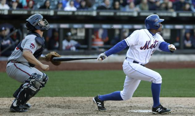 Atlanta Braves catcher Evan Gattis, left, looks after New York Met's Curtis Granderson's sacrifice fly during the fourteenth inning of the baseball game at Citi Field, Sunday, April 20, 2014 in New York. The Mets defeated the Braves in extra innings 4-3. (AP Photo/Seth Wenig)