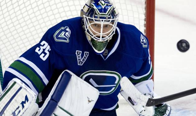 Vancouver Canucks goalie Cory Schneider (35) makes a save against the Calgary Flames during the second period of their NHL hockey game, Saturday, Feb. 9, 2013, in Vancouver, British Columbia. (AP Photo/The Canadian Press, Jonathan Hayward)