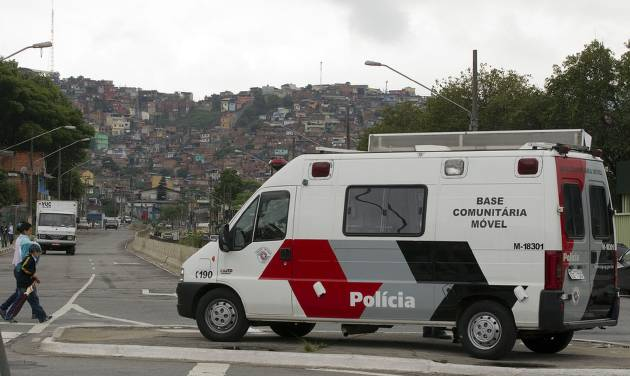 A police vehicle sits parked near the Brasilandia slum, behind, in Sao Paulo, Brazil, Wednesday, Nov. 14, 2012. The city has seen nearly 150 homicides in the past two weeks, including a 13-year-old boy and a female police officer in the violent Brasilandia slum. South America's biggest city is living its most violent days in six years, as a powerful drug gang and police carry out what security experts call retribution killings against one another. (AP Photo/Andre Penner)