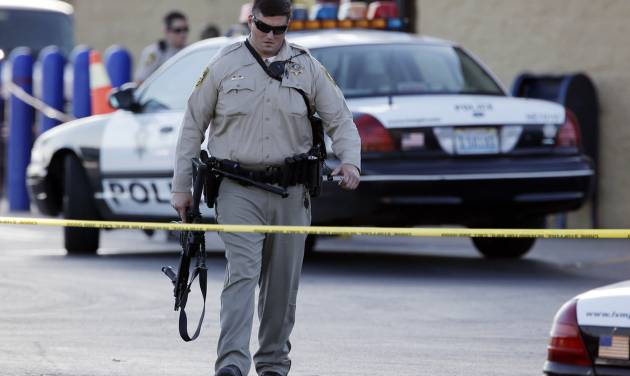 FILE - In this Sunday, June 8, 2014, file photo, a Las Vegas police officer walks away from the scene of a shooting near a Wal-Mart, in Las Vegas. At a time when shootings seem to happen almost daily, how should Americans react if someone opens fire at work, at school or at a theater or store? The Associated Press consulted experts on what to do. (AP Photo/John Locher, File)