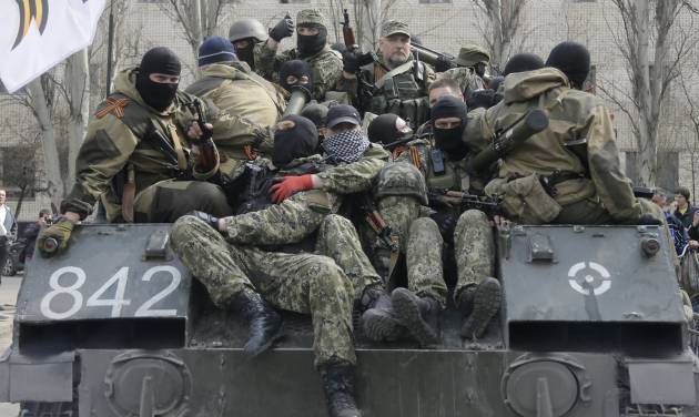 A combat vehicle with pro-Russian gunman on top runs through downtown Slovyansk on Wednesday, April 16, 2014. The troops on those vehicles wore green camouflage uniforms, had automatic weapons and grenade launchers and at least one had the St. George ribbon attached to his uniform, which has become a symbol of the pro-Russian insurgency in eastern Ukraine. (AP Photo/Efrem Lukatsky)