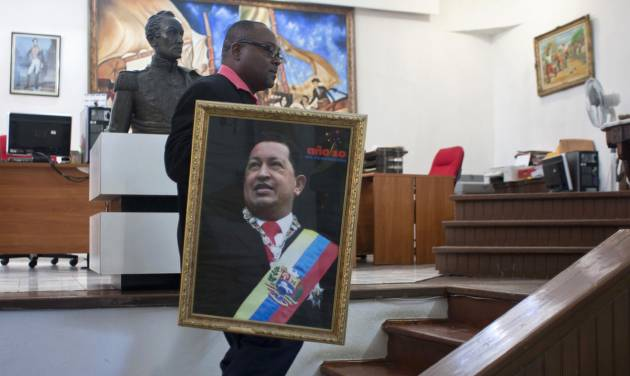 Pierre Denis, who works at Venezuela's embassy, carries an image of Venezuela's President Hugo Chavez after holding a Mass to pray for Chavez's health in Petion-Ville, Haiti, Friday, Dec. 21, 2012. Chavez is recovering in Cuba from surgery, his fourth operation related to pelvic cancer since June 2011. (AP Photo/ Photo/Dieu Nalio Chery)
