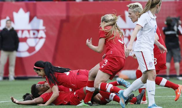 Canada's defender Kadeisha Buchanan, bottom left, celebrates her goal with forward Jonelle Filigno (16) and her teammates as United States' midfielder Heather O'Reilly (9) looks on during first half of an exhibition soccer match in Winnipeg, Manitoba, Thursday, May 8, 2014. (AP Photo/The Canadian Press, John Woods)