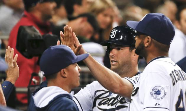 San Diego Padres' Seth Smith is greeted in the dugout after scoring in the fifth inning against the Cincinnati Reds in a baseball game Tuesday, July 1, 2014, in San Diego. (AP Photo/Lenny Ignelzi)