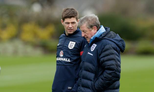 England captain Steven Gerrard, left, chats with manager Roy Hodgson during a national soccer squad training session at the training facilities of Tottenham Hotspur football club in Enfield, England, Monday, March 3, 2014. England play Denmark in an international friendly soccer match at Wembley stadium in London on Wednesday. (AP Photo/Matt Dunham)