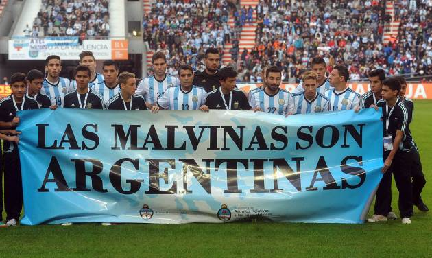 "Argentina's team poses for a picture with a banner reading in Spanish ""The Malvinas are Argentine"" referring to the Malvinas Islands or the Falkland Islands before an international friendly soccer match against  Slovenia in La Plata, Argentina, Saturday, June 7, 2014.(AP Photo/Raul Ferrari- Telam)"