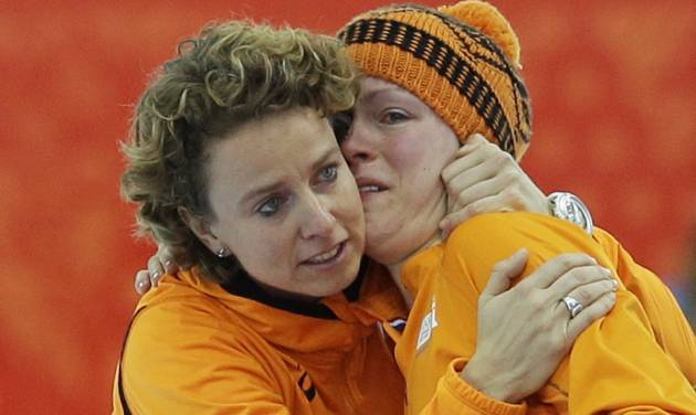 An emotional Jorien ter Mors of the Netherlands, right, is hugged by team member Renate Groenwold after she won gold for the women's 1,500-meter speedskating race at the Adler Arena Skating Center during the 2014 Winter Olympics in Sochi, Russia, Sunday, Feb. 16, 2014. (AP Photo/Patrick Semansky)