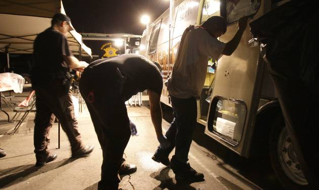 """FILE - In this July 29, 2010 file photo, Maricopa County Sheriff's deputies, left, check the shoes of a suspect arrested during a crime suppression sweep in Phoenix. A judge in Arizona on Tuesday, Sept. 18, 2012 ruled that police can immediately start enforcing the most contentious section of the state's immigration law, marking the first time officers can carry out the so-called """"show me your papers"""" provision. (AP Photo/Ross D. Franklin, File)"""