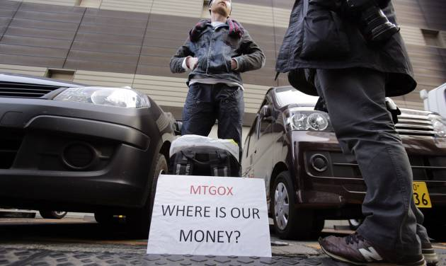FILE - In this Wednesday, Feb. 26, 2014 file photo, Bitcoin trader Kolin Burges stands in protest outside an office building housing Mt. Gox in Tokyo. Bankrupt bitcoin exchange Mt. Gox said it found 200,000 bitcoins, which were previously thought stolen, in disused electronic wallets. Another 650,000 bitcoins still remain unaccounted for. (AP Photo/Shizuo Kambayashi, File)