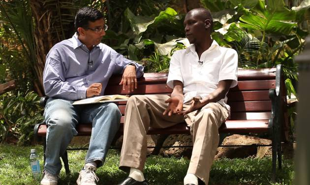 """FILE - In this publicity image released by Rocky Mountain Pictures, director Dinesh D'Souza, interviews George Obama in his film, """"2016: Obama's America.""""  D'Souza has been indicted in New York on charges he violated campaign finance laws. Federal prosecutors announced the charges Thursday, Jan. 23, 2014 against D'Souza, and say he'll be arraigned Friday on charges he directed $20,000 in illegal contributions to be made in the New York Senate race in 2012. (AP Photo/Rocky Mountain Pictures, File)"""