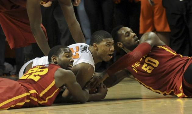 Iowa State's Dustin Hogue (22) and DeAndre Kane (50) tie up Oklahoma State's Marcus Smart (33) to take the game into a third overtime in an NCAA college basketball game in Stillwater, Okla., Monday, Feb. 3, 2014. Smart scored 20 points in the 97-98 loss to Iowa State. (AP Photo/Brody Schmidt)