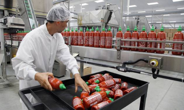 FILE - In this Oct 29, 2013 file photo, Sriracha chili sauce is produced at the Huy Fong Foods factory in Irwindale, Calif. A Los Angeles suburb is spicing up its lawsuit against this hot sauce manufacturer it claims polluted the air with pungent smells. An attorney representing the city of Irwindale, Calif., says the city will add a breach-of-contract claim to its existing nuisance suit against the Sriracha plant. (AP Photo/Nick Ut, File)