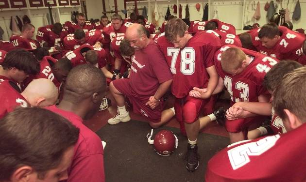Wynnewood coach Bruce Hendrickson and players have a prayer in the locker before a 1999 game after the death of Daniel Knowles. PHOTO BY BRYAN TERRY, THE OKLAHOMAN ARCHIVES