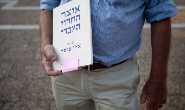 "In this Wednesday, June 13, 2012 photo, Israeli author Eli Tziper holds a copy of his book ""The treasure of the Hebrew rhyme"" at the Hebrew Book Week Fair in Tel Aviv. In the land of the People of the Book, the discounted book may soon be a thing of the past. Israeli authors have launched a battle to stop the country?s two leading bookstore chains from discounting their works, claiming the price slashing has cut into their royalties. (AP Photo/Ariel Schalit)"