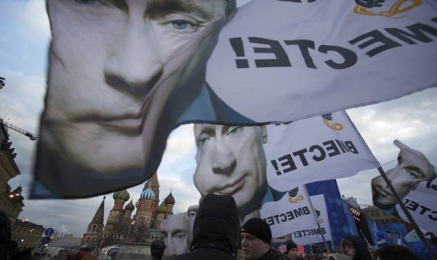 """People rally in support of Crimea joining Russia, with banners and portraits of Russian President Vladimir Putin, reading """"We are together,"""" in Red Square in Moscow, Tuesday, March 18, 2014.  With a sweep of his pen, President Vladimir Putin added Crimea to the map of Russia on Tuesday, describing the move as correcting past injustice and responding to what he called Western encroachment upon Russia's vital interests. (AP Photo/Pavel Golovkin)"""