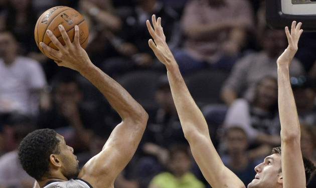San Antonio Spurs forward Tim Duncan, left, shoots against New Orleans Pelicans center Jeff Withey during the first half of an NBA basketball game on Saturday, March 29, 2014, in San Antonio. (AP Photo/Darren Abate)