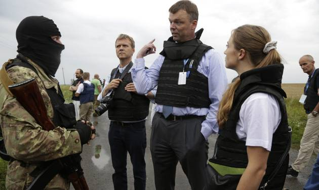 Representatives from the Organization for Security and Cooperation speak to a pro-Russia fighter at the crash site of a Malaysia Airlines jet near the village of Hrabove, Friday, July 18, 2014. Representatives from the Organization for Security and Cooperation in Europe and four Ukrainian experts had traveled into rebel-controlled areas to begin an investigation into the attack that killed 298 people from nearly a dozen nations. (AP Photo/Dmitry Lovetsky)