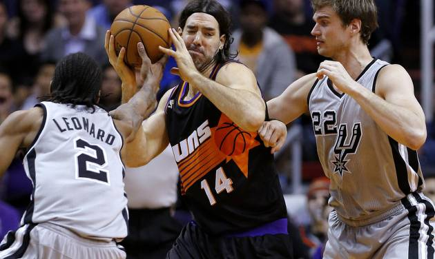 San Antonio Spurs' Kawhi Leonard (2) and Tiago Splitter (22), of Brazil, pressure Phoenix Suns' Luis Scola (14), of Argentina, during the first half of an NBA basketball game, Sunday, Feb. 24, 2013, in Phoenix. (AP Photo/Matt York)