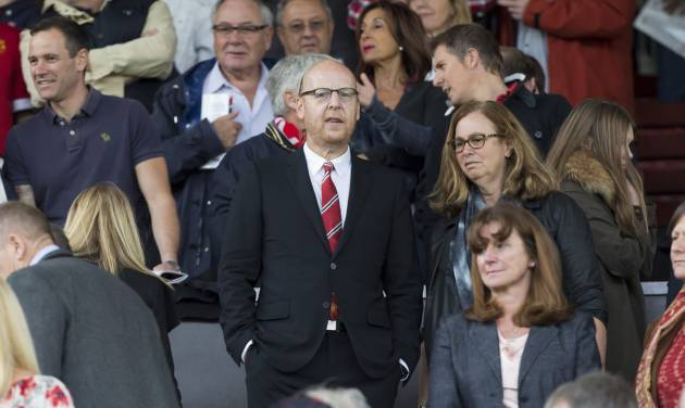 Manchester United's joint chairman Avram Glazer, center, takes his seat in the stands before the team's English Premier League soccer match against Swansea City at Old Trafford Stadium, Manchester, England, Saturday Aug. 16, 2014. (AP Photo/Jon Super)