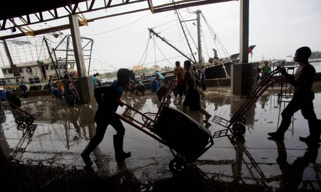 Migrant workers unload frozen fish from a boat at a fish market in Samut Sakhon Province, west of Bangkok, Friday, June 20, 2014. The United States has blacklisted Thailand and Malaysia for failing to meet its minimum standards in fighting human trafficking, a move that could strain relations with two important U.S. partners in Asia. Thailand had mounted a determined campaign to prevent a downgrade that could exact a reputational cost on its lucrative seafood and shrimp industries for which America is a key market. (AP Photo/Sakchai Lalit)