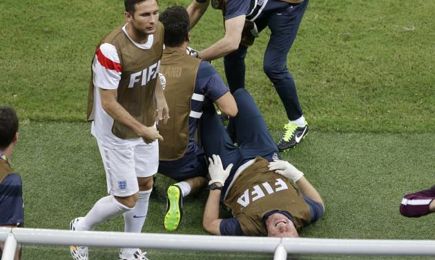 Frank Lampard, left, walks past as an English staff member grimaces in pain during the group D World Cup soccer match between England and Italy at the Arena da Amazonia in Manaus, Brazil, Saturday, June 14, 2014.  (AP Photo/Themba Hadebe)