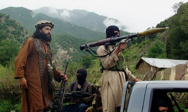 "FILE - In this file photo taken on Aug. 5, 2012, Pakistani Taliban patrol in their stronghold of Shawal in Pakistani tribal region of South Waziristan. The Pakistani army said it has launched a ""comprehensive operation"" against foreign and local militants in a tribal region near the Afghan border. An army statement issued Sunday, June 15, 2014 said the long-awaited offensive in North Waziristan was started at the direction of the government of Pakistan. (AP Photo/Ishtiaq Mahsud, File)"
