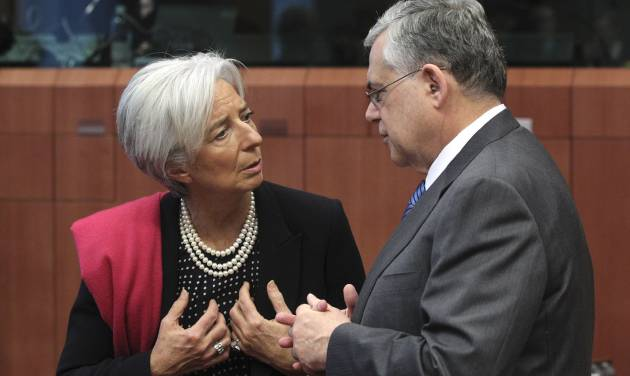 Managing Director of the International Monetary Fund Christine Lagarde, left, speaks with Greek Prime Minister Lucas Papademos during a round table meeting of eurozone finance ministers at the EU Council building in Brussels on Monday, Feb. 20, 2012. Eurozone governments will likely approve on Monday a long-elusive rescue package for Greece, saving it from a potentially calamitous bankruptcy next month, senior officials said. But finance ministers meeting in Brussels will have a few last issues to wrangle over, such as tighter controls over Greece's spending and further cuts to the country's debt load. (AP Photo/Yves Logghe)