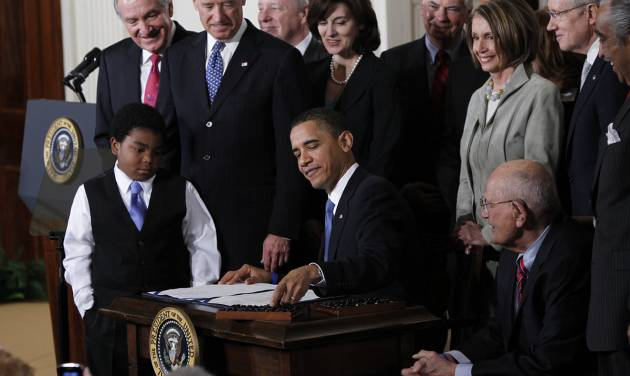 "FILE - In this March 23, 2010, file photo, President Barack Obama reaches for a pen to sign the health care bill in the East Room of the White House in Washington. Obama's re-election has guaranteed the survival of his health care law. Now the administration is in a sprint to the finish line to put it into place. In just 11 months, millions of uninsured people can start signing up for coverage. But there are hurdles in the way. Republican governors will have to decide whether they can join the team and help carry out what they've dismissed as ""Obamacare."" And the administration could stumble under the sheer strain of implementing the complex legislation, or get tripped up in budget talks with Congress. (AP Photo/Charles Dharapak, File)"
