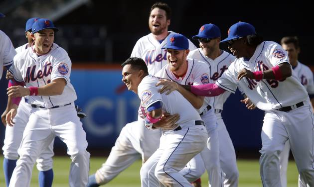New York Mets' Ruben Tejada, center, gets a hug from Zack Wheeler as he is mobbed by teammates after hitting a game-winning RBI single during the eleventh inning of a baseball game against the Philadelphia Phillies, Sunday, May 11, 2014, in New York.  New York won 5-4 in eleven innings. (AP Photo/Jason DeCrow)