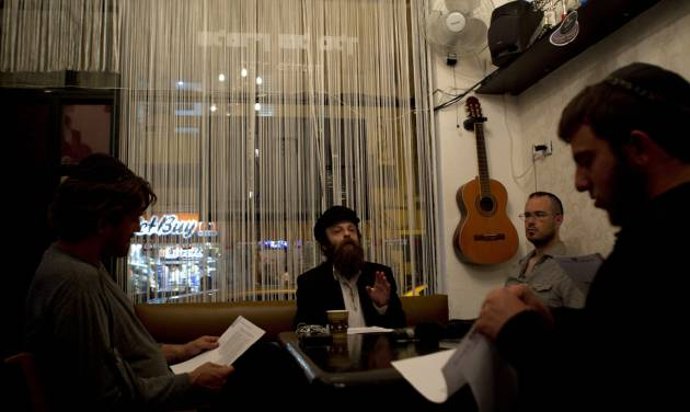 In this photo taken on Tuesday, Dec. 4, 2012, Shmuel Fortman Hapartzy, the Cain and Abel School for Prophets founder and teacher speaks to students in Tel Aviv, Israel. Instead of long beards and robes, they wear track suits and T-shirts. Their tablets are electronic, not hewn of stone, and they hold smartphones, not staffs. They may not look the part, but this ragtag group of Israelis is training to become the next generation of prophets. For just 200 shekels ($53) and in only 40 short classes, anyone can become a certified, modern-day soothsayer at the Cain and Abel School for Prophets.(AP Photo/Ariel Schalit)