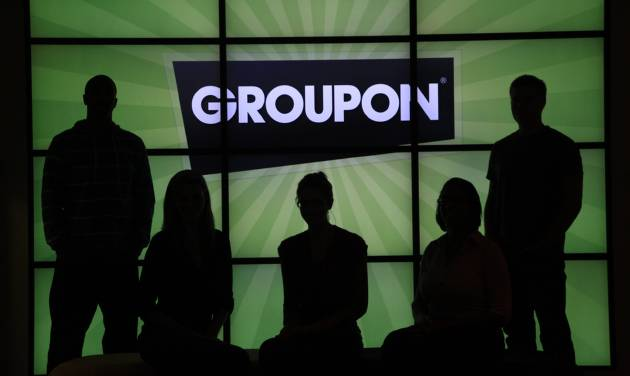 """In this Thursday, Sept. 22, 2011, photo, employees at Groupon pose in silhouette by the company logo in the lobby of the online coupon company's Chicago offices. Groupon Inc., the No. 1 online deals service, failed to show investors on Thursda, Nov. 8, 2012, that its business is growing as quickly as they would like, as it was hurt by what it called """"continued challenges"""" from the economic weakness in Europe. (AP Photo/Charles Rex Arbogast)"""