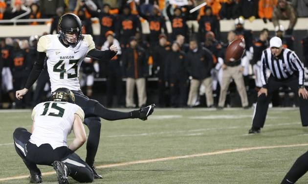 Baylor kicker Aaron Jones (43) kicks a field goal against Oklahoma State in the second quarter of an NCAA college football game in Stillwater, Okla., Saturday, Nov. 23, 2013. Baylor's Brody Trahan (15) holds. (AP Photo/Sue Ogrocki)