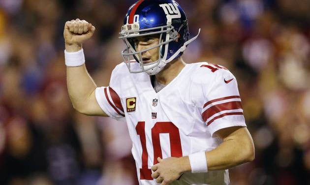 New York Giants quarterback Eli Manning celebrates a touchdown pass to tight end Martellus Bennett during the first half of an NFL football game against the Washington Redskins in Landover, Md., Monday, Dec. 3, 2012. (AP Photo/Patrick Semansky)