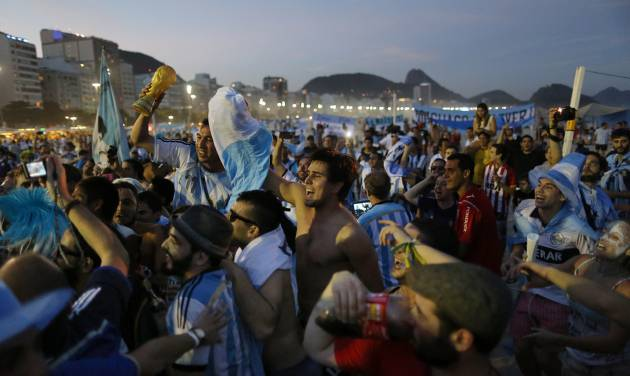 Argentine soccer fans celebrate, one day before the 2014 Soccer World Cup debut of their team, on Copacabana beach, in Rio de Janeiro, Brazil, Saturday, June 14, 2014. Argentina will play in group F of the tournament. (AP Photo/Leo Correa)