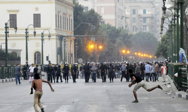Egyptian protesters hurl stones at riot police in downtown Cairo, Egypt, early Saturday, Sept. 15, 2012, before police cleared the area after days of protests against a film ridiculing the Prophet Muhammad. Egyptian police on Saturday cleared out protesters who have been clashing with security forces for the past four days near the U.S. Embassy as most cities around the Muslim world reported calm a day after at least six people were killed in a wave of angry protests over an anti-Islam film.(AP Photo)
