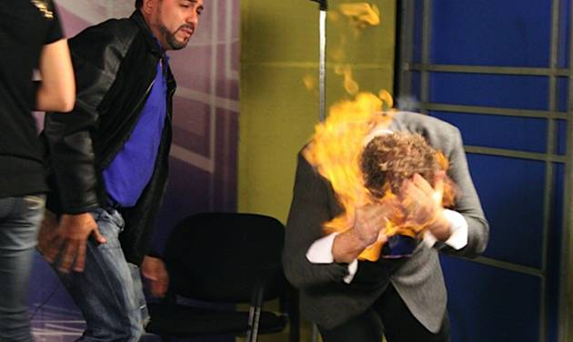 "In this picture released by American magician Wayne Houchin, Dominican TV presenter Franklin Barazarte, left, watches as Houchin's head burns while taping ""Closer To The Stars"" TV program in Santo Domingo, Dominican Republic, Monday, Nov. 26, 2012. Houchin, of Chico, California, is receiving treatment for burns after the incident where Barazarte lit his head on fire with a flammable cologne. (AP Photo)"
