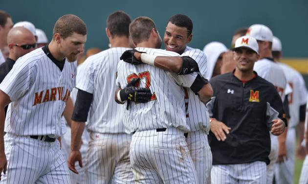 Maryland's Jose Cuas, center, hugs teammate Kyle Convissar (22) after Maryland defeated Old Dominion 4-3 during an NCAA college baseball tournament regional game in Columbia, S.C.,  Friday, May 30, 2014. (AP Photo/Richard Shiro)