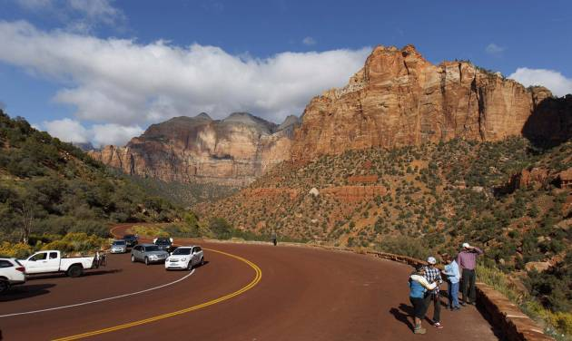 In this Friday, Oct. 11, 2013 photo, visitors to Zion National Park take in the sights after the park opened on a limited basis. Thousands of hikers, bikers and nature-lovers traveled to Utah's red rock national parks this weekend as they were reopened for the first time since the partial government shutdown began Oct. 1. (AP Photo/The Salt Lake Tribune, Trent Nelson)  DESERET NEWS OUT; LOCAL TV OUT; MAGS OUT