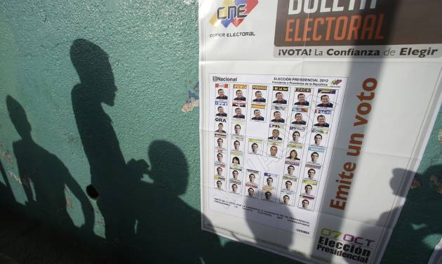 Voters' shadows are cast on a wall as they wait at a polling station during the presidential election in Caracas, Venezuela, Sunday, Oct. 7, 2012. President Hugo Chavez is running against opposition candidate Henrique Capriles. (AP Photo/Fernando Llano)