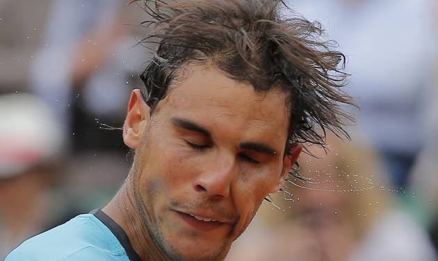 Spain's Rafael Nadal shakes the sweat off his head after winning his fourth round match of the French Open tennis tournament against Serbia's Dusan Lajovic at the Roland Garros stadium, in Paris, France, Monday, June 2, 2014. Nadal won in three sets 6-1, 6-2, 6-1. (AP Photo/Michel Spingler)